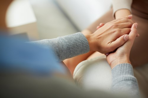 Woman reassuring her friend by holding her hand during IVF appoinment